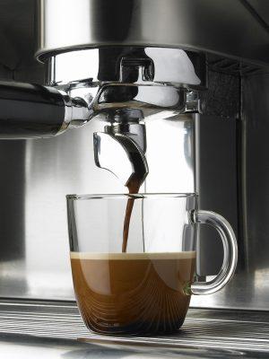 Detalle de elaboración de taza de café. Cafetera. Máquina de café. Cristalería