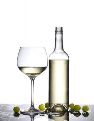 Dkristal - Detalle de copa de vino blanco junto a botella. Copa, botella, vino blanco, Vinoteca. Bodega