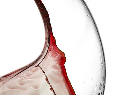 Detalle de decantador con chorro vino tinto.